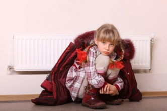 Little girl huddled under a coat