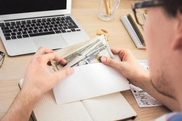 man putting money in envelope