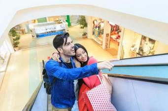 Young couple on escaltor in mall