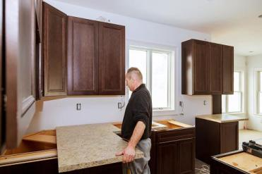 workman placing counter in kitchen