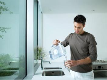 Man pouring water from filter pitcher