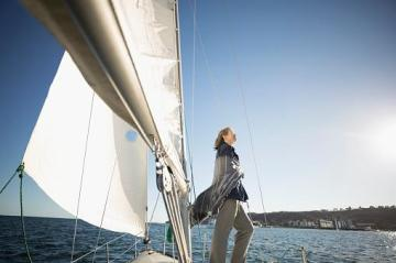 woman standing on deck of a sailboat