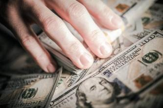 image of a hand on piles of money