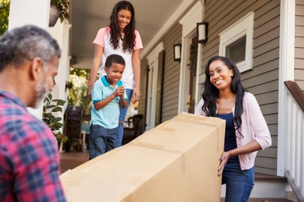 Family carrying large box into home