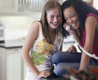 Two teen girls sharing a landline phone