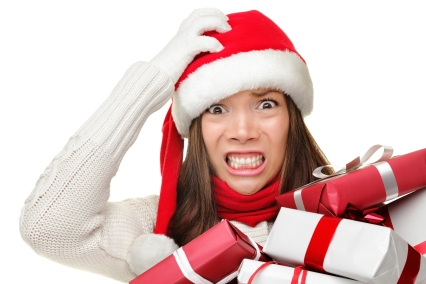 woman in santa hat with scary face and an armful of gifts
