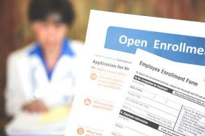 open enrollment forms over blurry background of medical professional