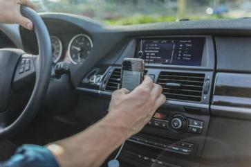 Hand holding moble phone on dashboard of car