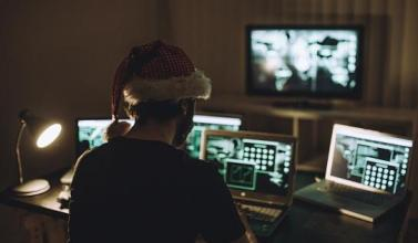 Man sitting among computers with santa hat on
