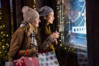 Two women looking in window holiday shopping