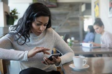 woman in coffee shop checking cell screen