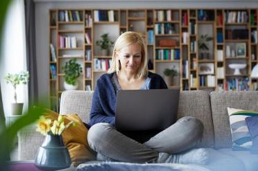 Woman sitting on sofa with a laptop