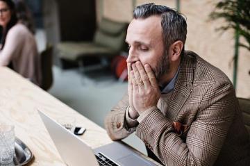 man looking at computer and looking upset