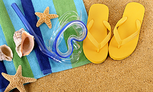 flip flops and sea shells on beach towel