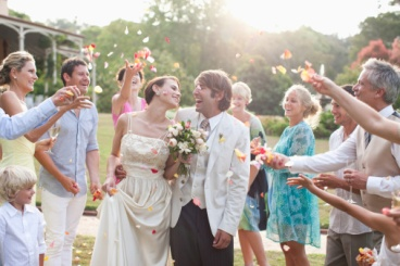 guests tossing flowers at wedding couple