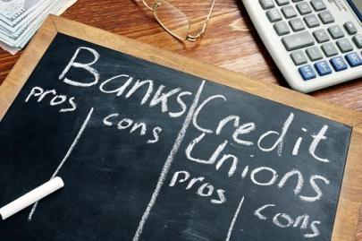 blackboard with columns for banks and credit union pros and cons