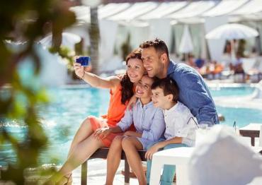 family taking selfie by a pool
