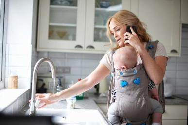 woman with a baby holding a phone