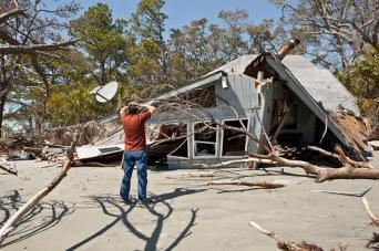 man viewing damage to his house