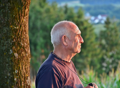 older man holding binoculars in the woods