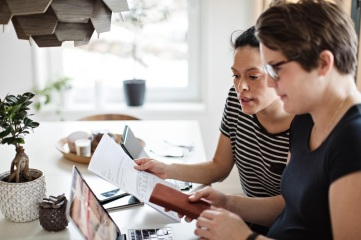 two women looking at a laptop and bank statement