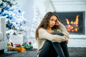 girl sitting in front of fireplace looking stressed