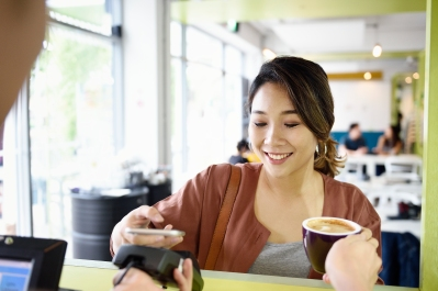 Woman using her phone to make payment in a cafe