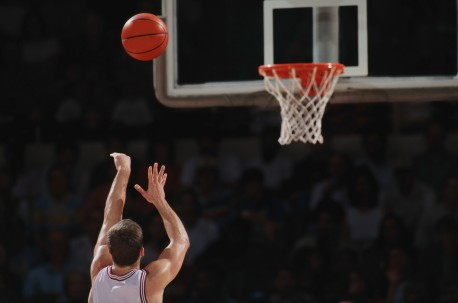 Basketball player shooting from free throw line, rear view