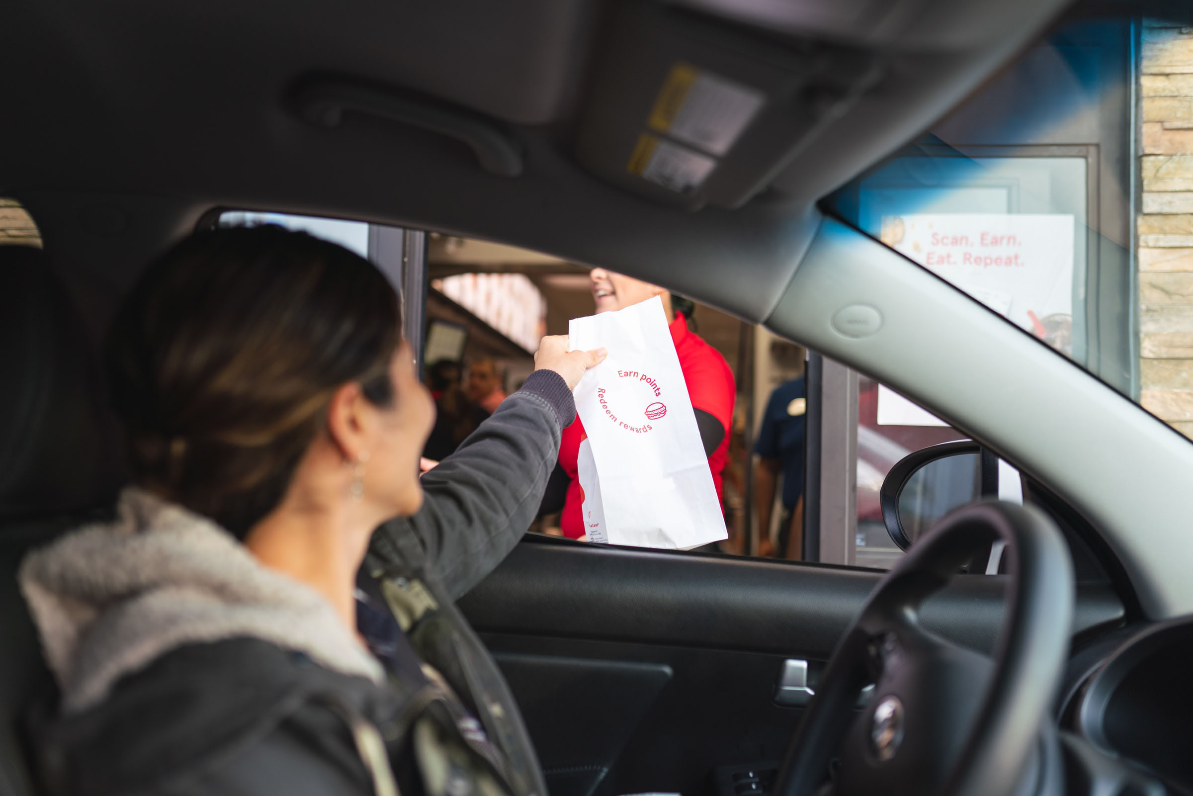 Woman in car picking up order from drive thru window