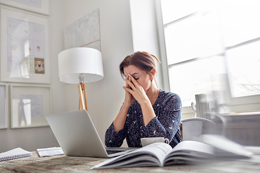woman looking overwhelmed in front of computer