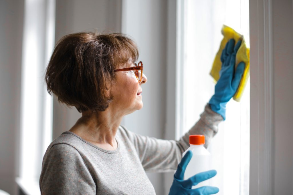 Woman with glasses wearing blue rubber gloves cleaning windows.