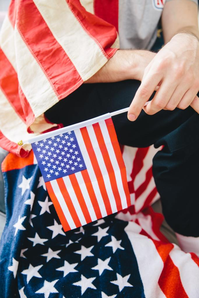 Man Holding American Flag in left hand, while draped in American flag.