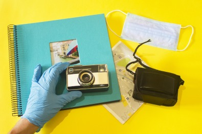 photo album and camera being held by a gloved hand