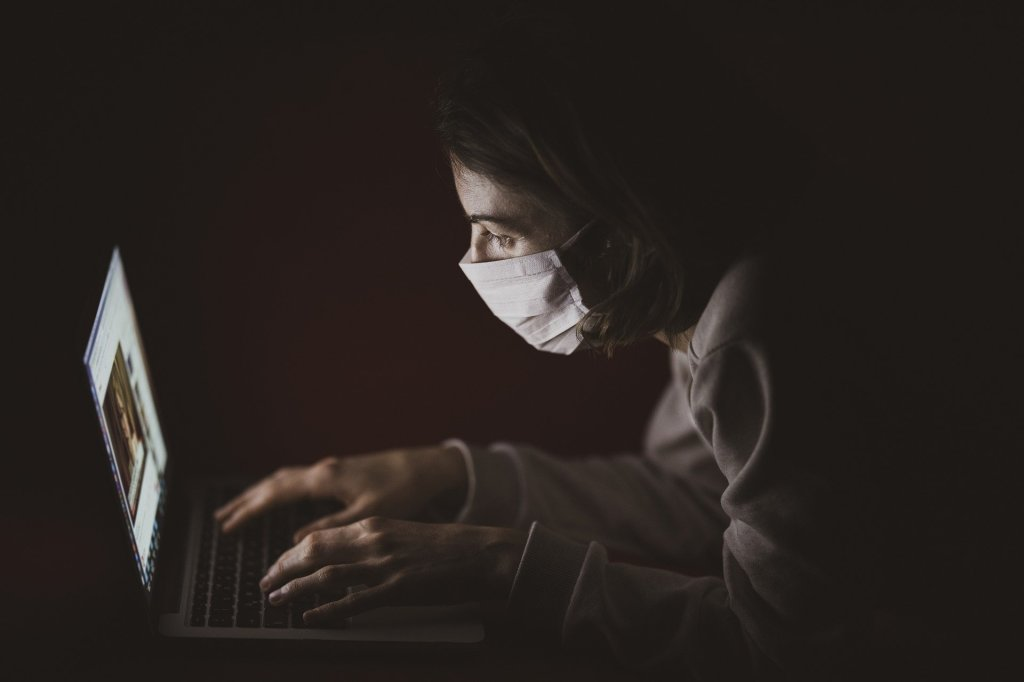 Woman in Mask Using Laptop.