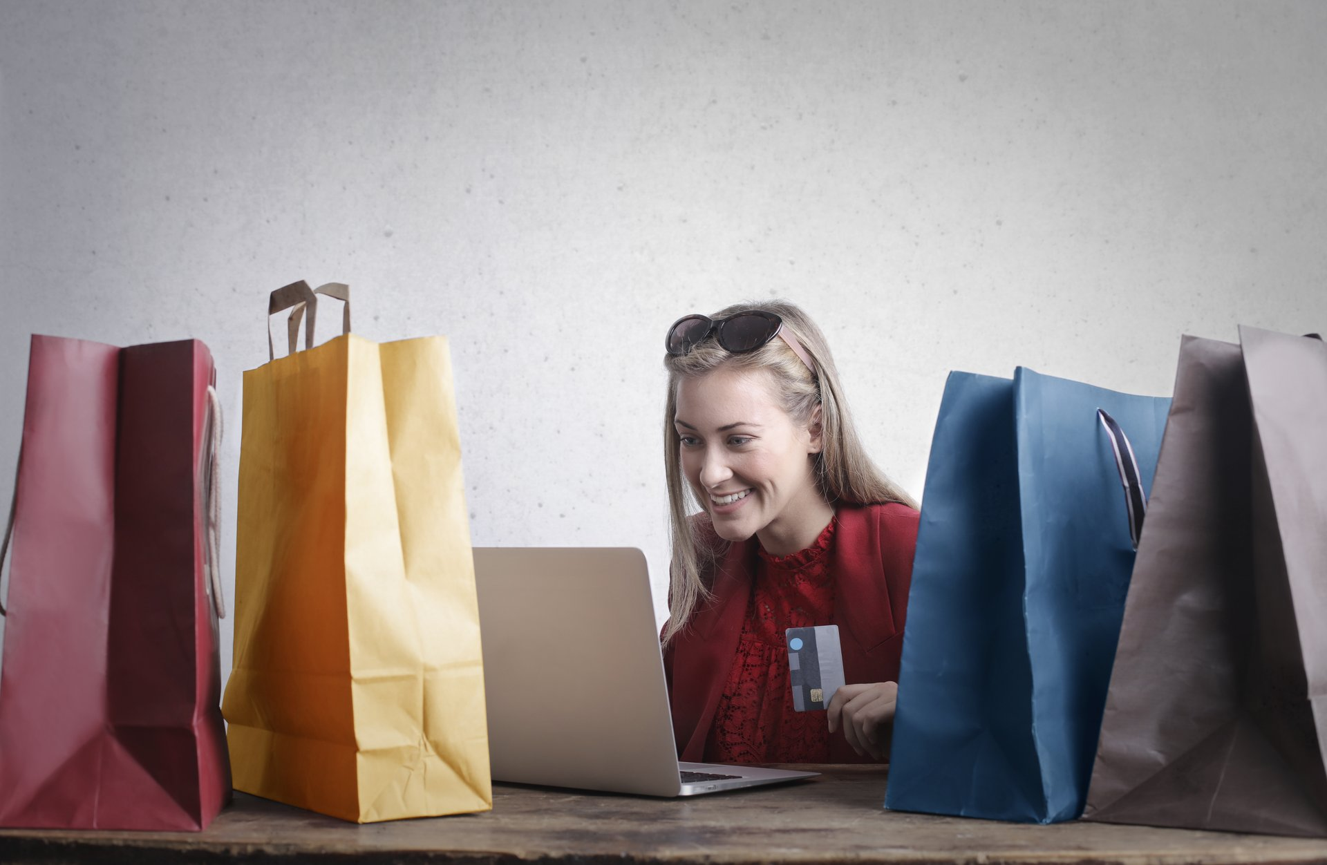 woman with credit card in hand surrounded by shopping bags