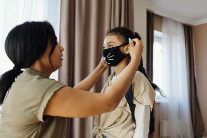 Mother putting mask on her daughter